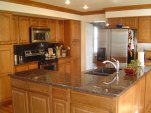 Kitchen with large island oak cabinets and granite tops